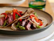 Tyler Florence's Fajitas recipe from Food Network features chipotle-marinated skirt steak, juicy peppers, onions, guacamole and warm flour tortillas.