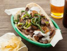 This loaded Philly cheesesteak recipe, from Throwdown with Bobby Flay on Food Network, is topped with a melted provolone sauce, onions, peppers and mushrooms.