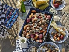 Whether you're vacationing in New England or elsewhere, summer is the time for an authentic, sea-soaked clambake on the beach.