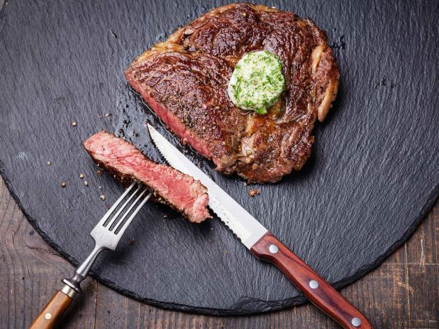 Medium rare grilled Beef steak with herb butter on fork on dark background