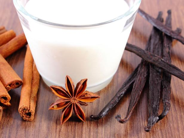 Fragrant vanilla, cinnamon sticks, star anise and glass of milk on wooden surface