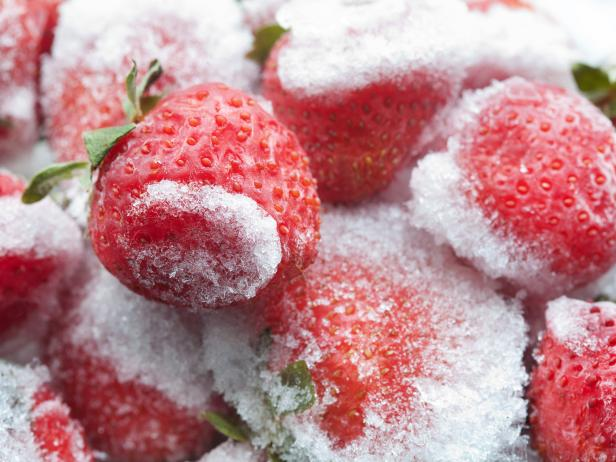 Frozen strawberries with green leaves closeup. Detailed cold fruit image. soft focus