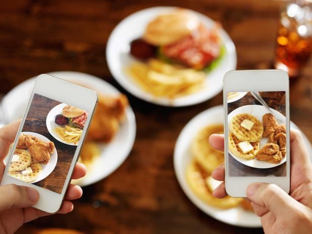two friends taking photo of their food with smartphones