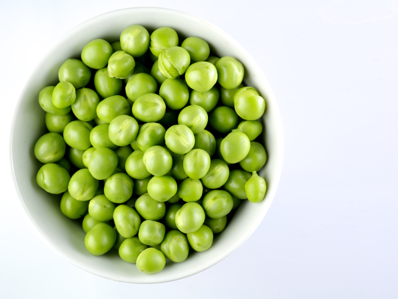 Green peas in the bowl isolated on white