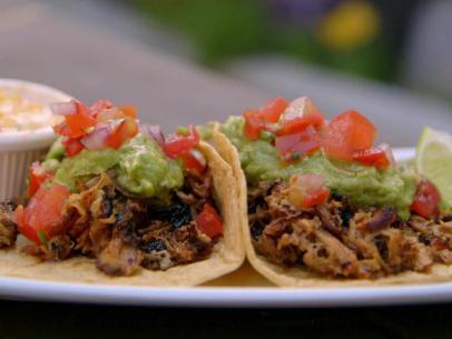 Carnitas tacos with pico de gallo and guac on top